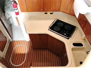 large galley with refrigerator, stove top, and sink