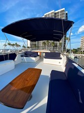 Helm deck seating, teak table, deck box, flybridge bimini
