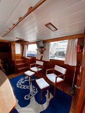 Salon looking portside aft, entry door, TV, GB chairs, teak handrail
