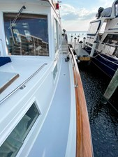 Port side deck with non-skid, teak cap rail SS handrail