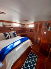 Owner's stateroom island queen and port locker, bureau, desk