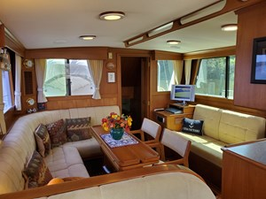 Settee and yacht table aft of helm seat, port side settee