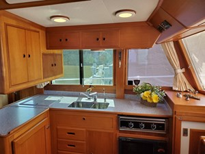 L galley with upper and lower cabinets, 3 burner range, SS sink with cover