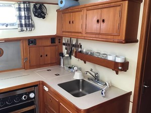 Galley forward end with upper cabinets, mug shelf, knife storage