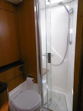 Forward shower has seating and hatch
