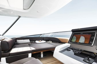 Seating area next to helm station on fly convertible in sunbathing area